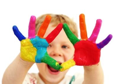 bambino con mani sporche di colore che gioca