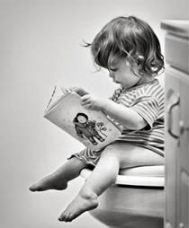bambino che legge un libro seduto in bagno sul wc