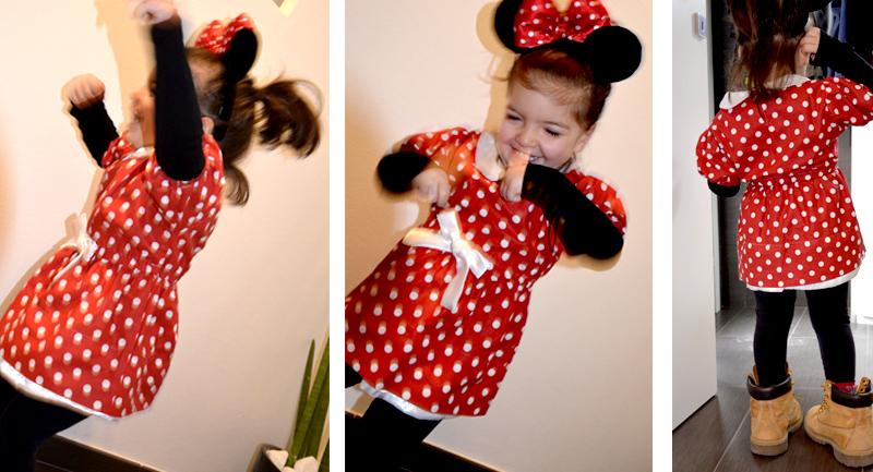 bimba balla felice e sorridente con vestito di carnevale di minnie con cerchietto con orecchie e fiocco a pois rosso e bianco