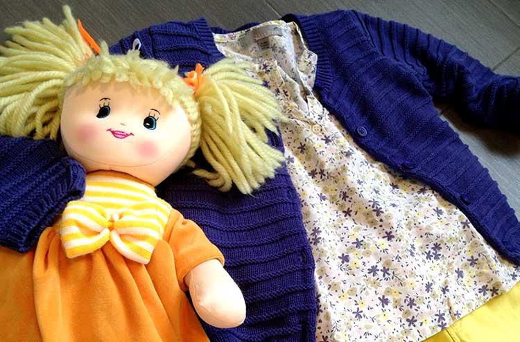 outfit colore bimba con jeans super skinny giallo, camicetta blusa a fiori, cardigan costine blu viola e bambola di pezza
