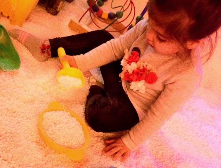 bambina che gioca con il sale come fosse sabbia nella stanza del sale per haloterapia