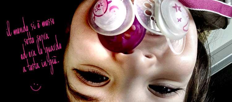 bambino sotto sopra a testa in giù con ciucci in bocca