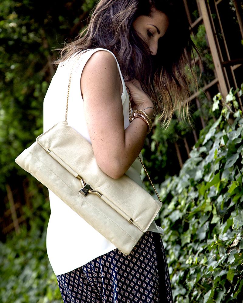 look outfit donna con borsa clutch bag vintage, pantaloni elasticizzati morbidi con micro stampa, gioielli oro e capelli con shatush