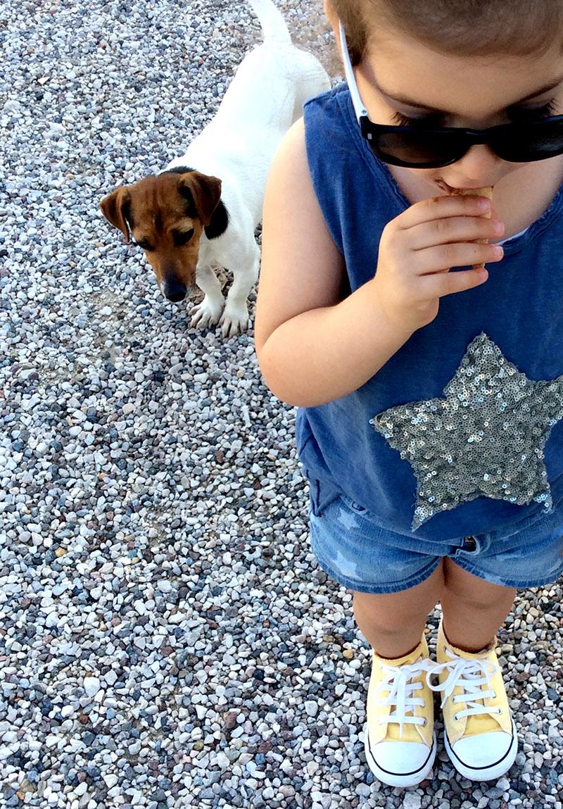 camicia tartan colori accesi, short in jeans denim con stelle e t-shirt cotone blu con stella paillettes, converse gialle per look bimba che mangia il gelato in compagnia di jack russel