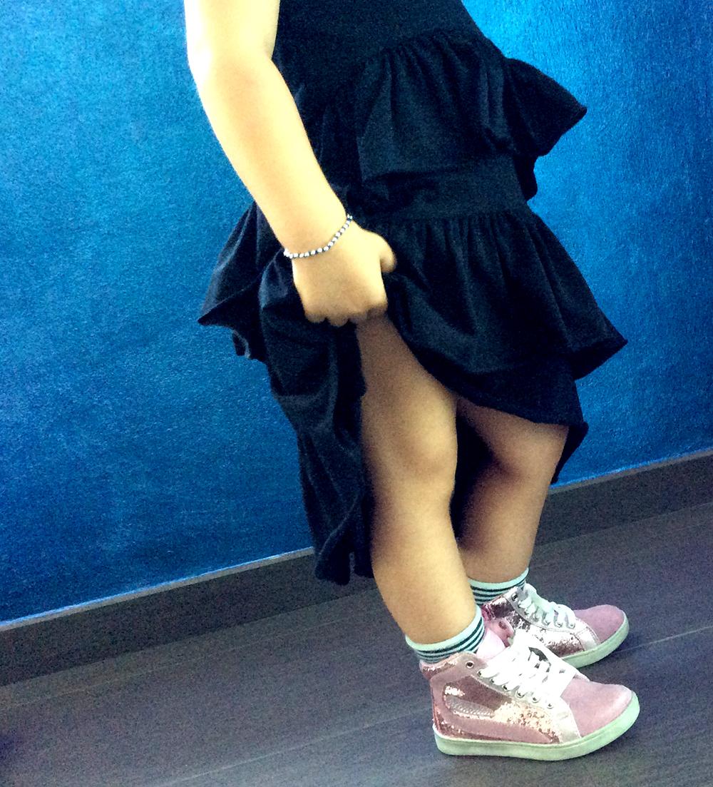dettaglio abito in cotone elasticizzato kloo by boose pequenoshop con balze e sneakers glitter rosa e calze a righe bianco e nero