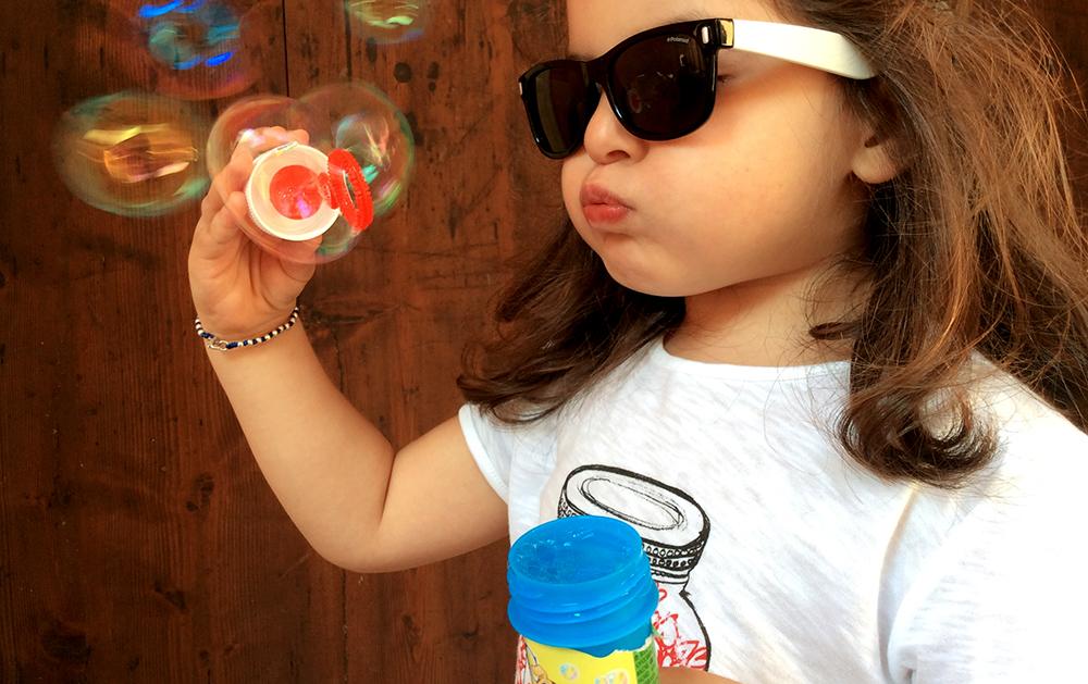 bambina gioca con bolle di sapone colorate e magiche con occhiali da sole polaroid e t-shirt zara barattolo cuoricini