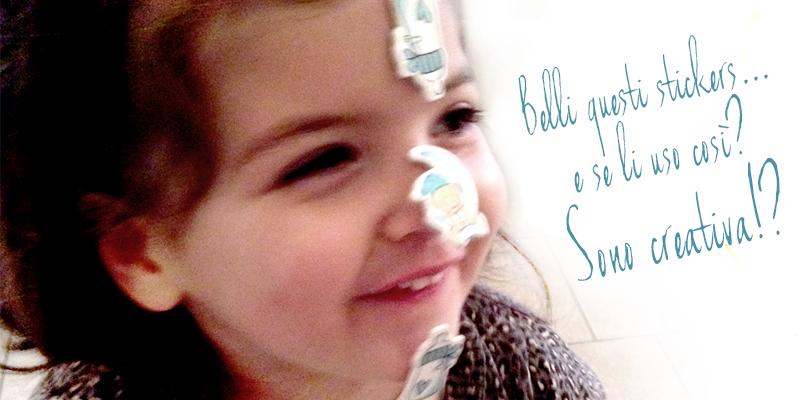 stimolare la creatività nei bambini, bimba gioca con stickers attaccandoseli in viso e sulla fronte