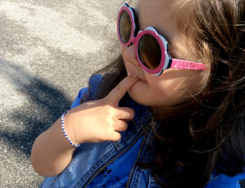 bambina kids girls con occhiali da sole zoo bug protezione solare 100% e look con gilet in jeans e t-shirt lion of leisure pequenoshop