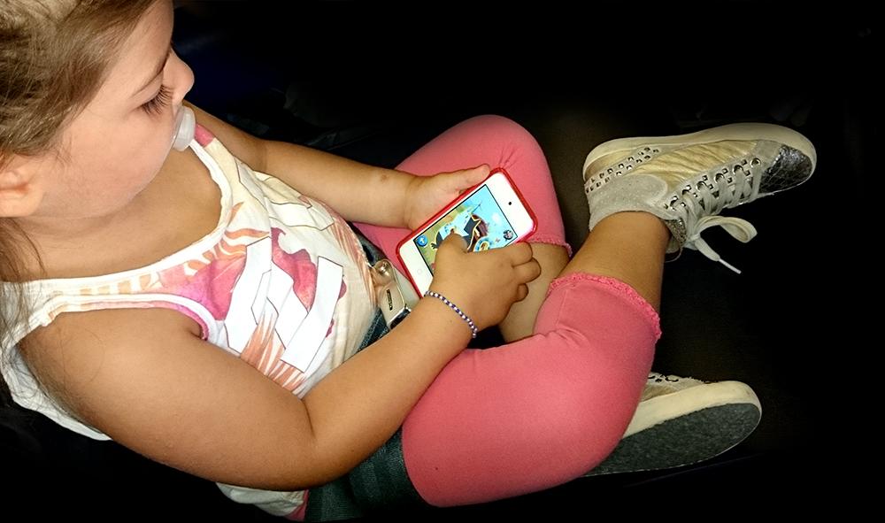 bambina con ciuccio gioca con app puzzle con smartphone in aereo