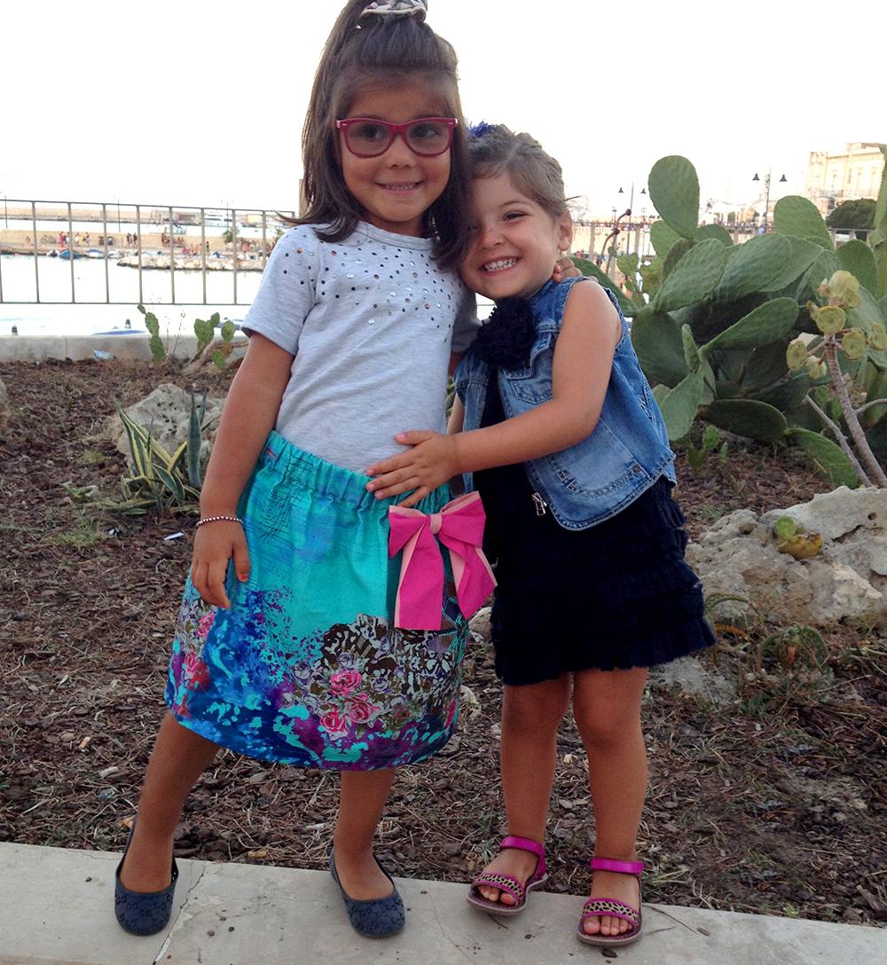 bambine amiche si abbracciano e sorridono durante una vacanza al mare in Puglia in salento