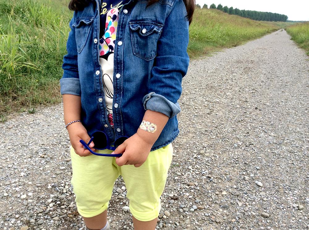 look bimba con t-shirt minnie disney blu e colori vivaci con pantaloni lime con risvolto sopra alla caviglia, camicia di jeans e snekers