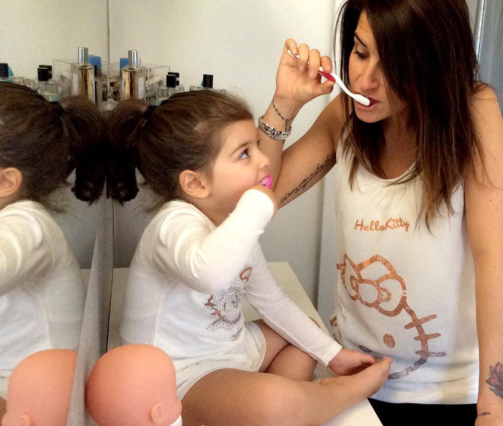 mamma e figlia sorridono e giocano lavandosi i denti in bagno per iniziare un nuovo giorno con il nuovo orario con l'ora solare in un look coordinato anche per la nanna