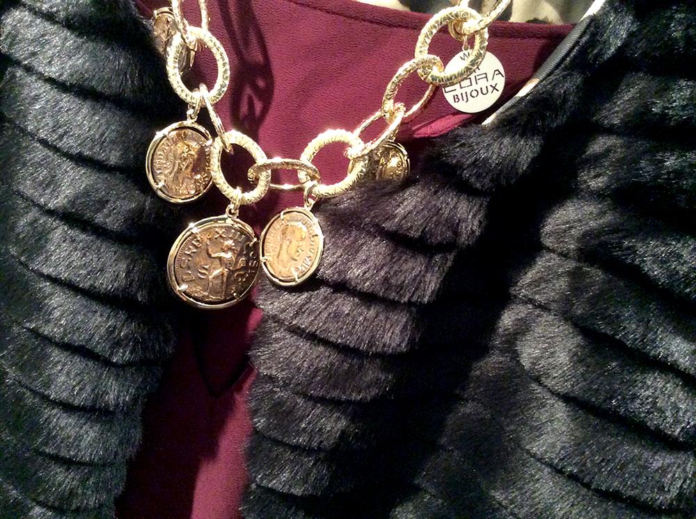 dettaglio gilet in ecopelliccia fatto a mano, blusa in seta bordeaux e collana oro cora bijoux con monete