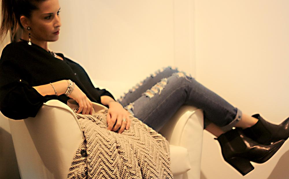 look fashion donna su poltrona pelle bianco, jeans stracciati ed accessori rosso prezioso