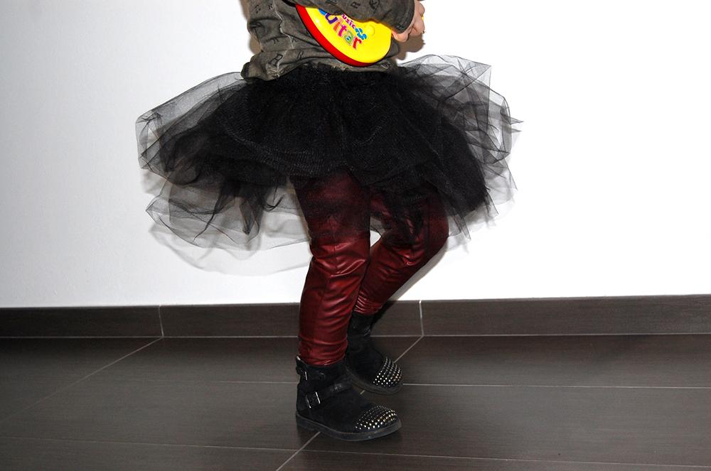 bambina gioca alla rockstar con chitarra giocattolo e look rock con gonna tulle e leggings ecopelle
