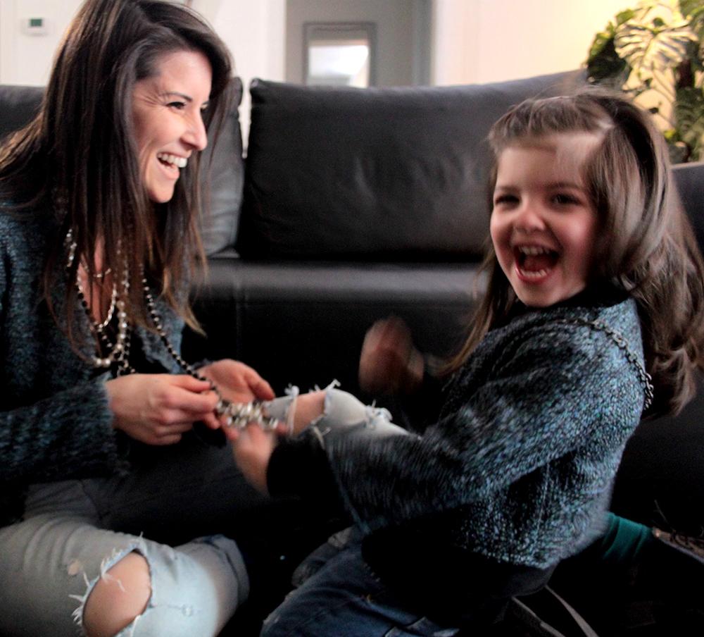 mamma e bimba che giocano con le collana della mamma e sorridono felici