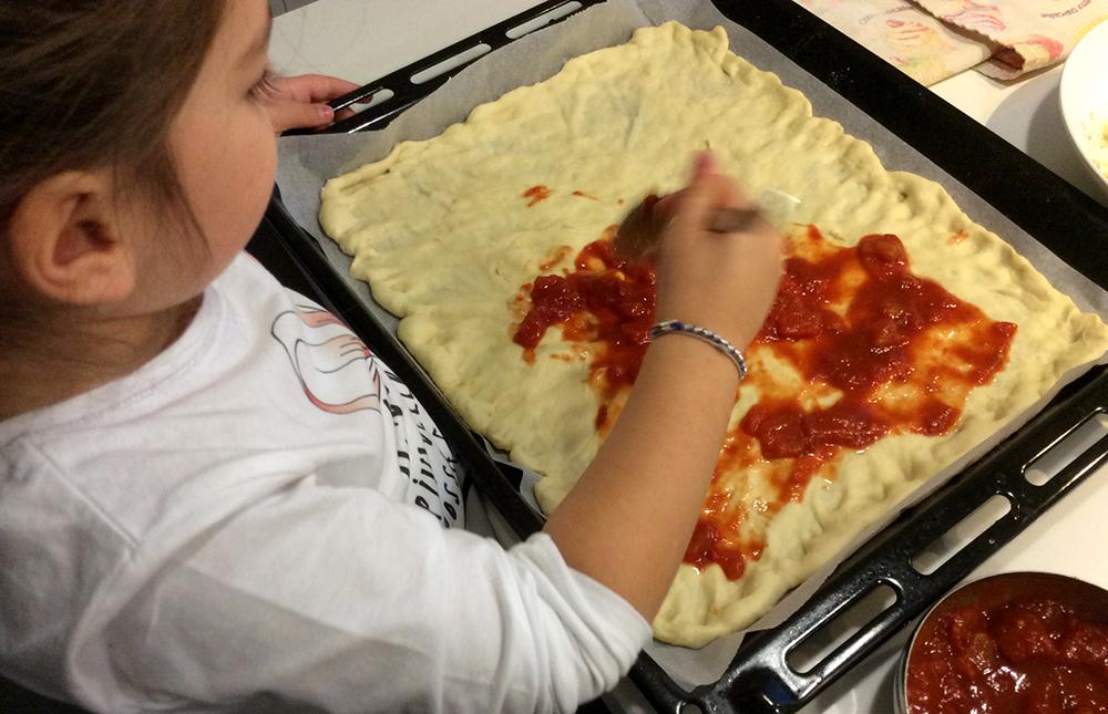 bimba prepara la pizza con la mamma stende il pomodoro sulla pasta nella teglia da forno