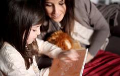 importanza leggere ai bambini, mamma e bimba leggono un libro nel lettone con tante coccole per una domenica mattina perfetta