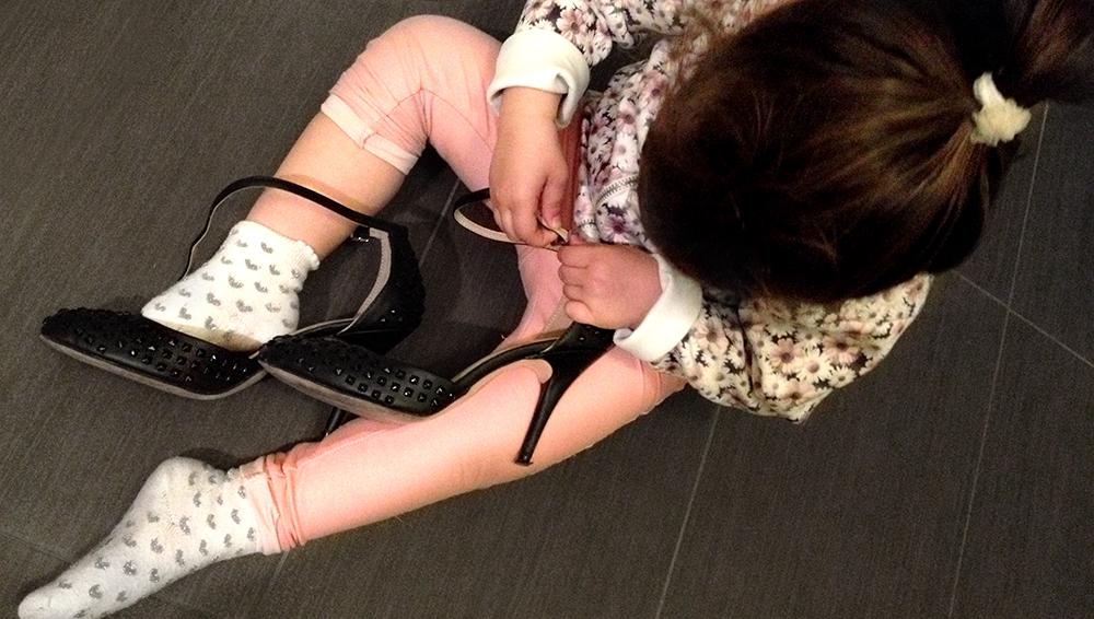 bambina autonoma infila le scarpe della mamma