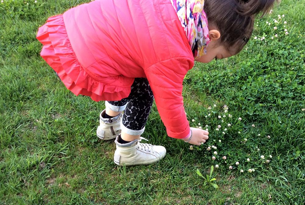 bambina raccoglie fiori in giardino con look glamour, giacca sarabanda, leggings jungle handmade folliefollie by mom&me e sneakers crime london