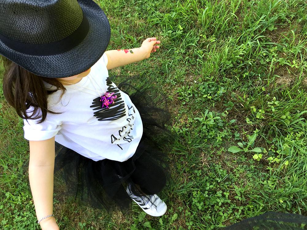 bambina cammina nel prato con gonna in tulle nero, adidas superstar, t-shirt con cuore amore della mamma e cappello panama nero catya