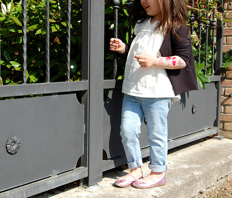 bambina tatuaggi trasferibili, jeans, ballerine, blusa bianca e cardigan nero