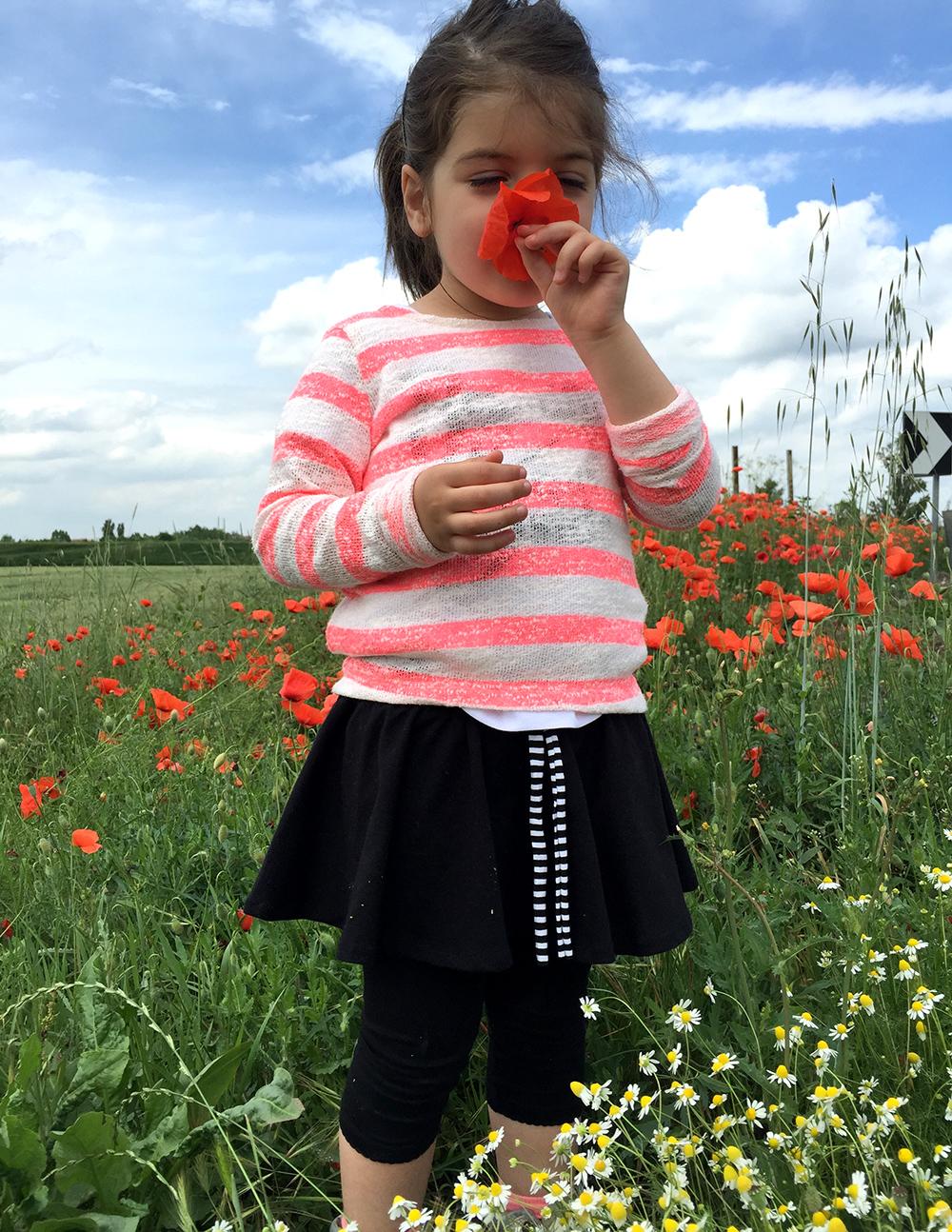 bambina annusa fiore di papavero in campagna con gonna realizzata a mano e maglia a righe