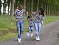 mamma, papà e bimba scherzano e giocano in look coordinato con jeans, t-shirt a righe e adidas superstar