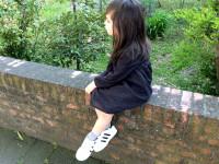 bambina seduta sul muretto con adidas originale superstar e abito tocoto vintage