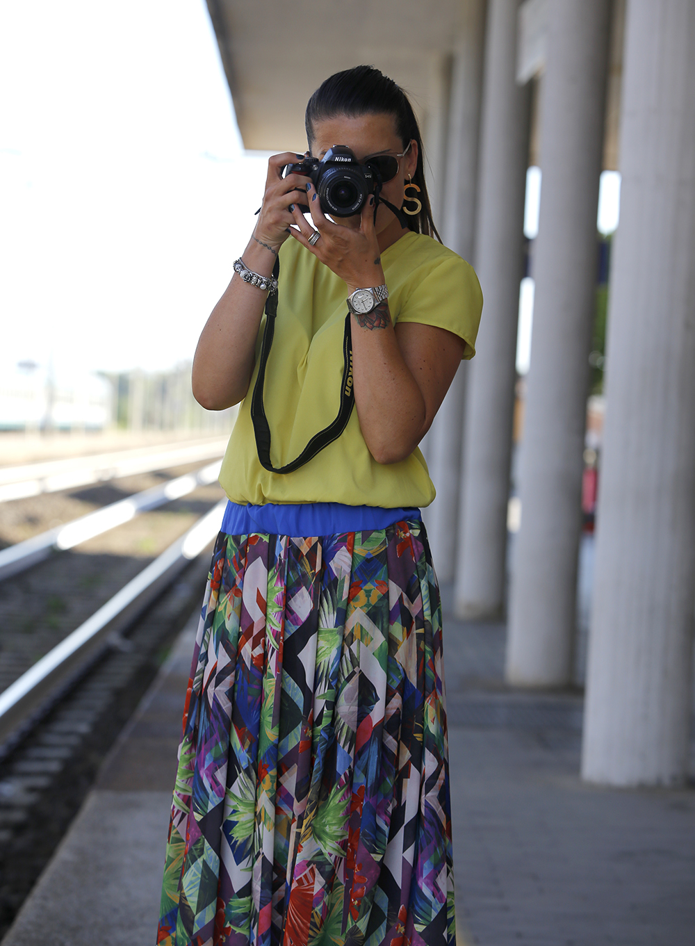 donna scatta foto con macchina fotografica nikon, gonna lunga a fantasia realizzata a mano e blusa giallo