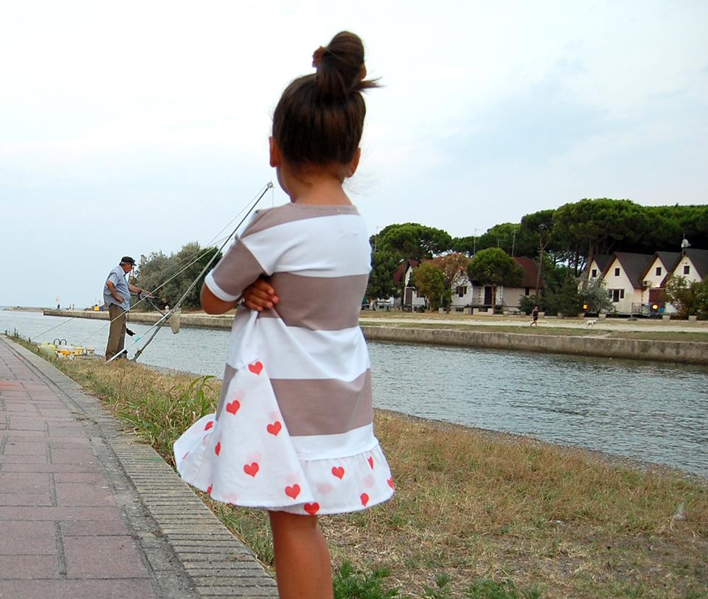 bambina osserva pescatore con abito a righe e cuori rossi