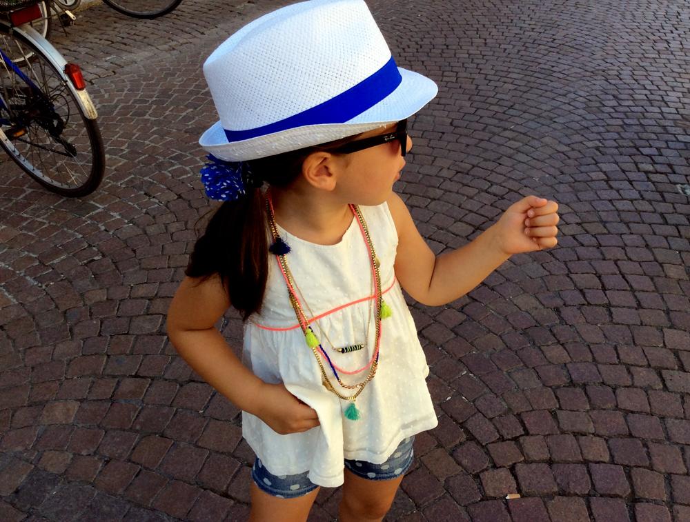 spunto outfit bambina, cappello panama bianco Catya, top bianco e short in jeans a pois, collana e occhiali da sole ray ban con lenti a specchio