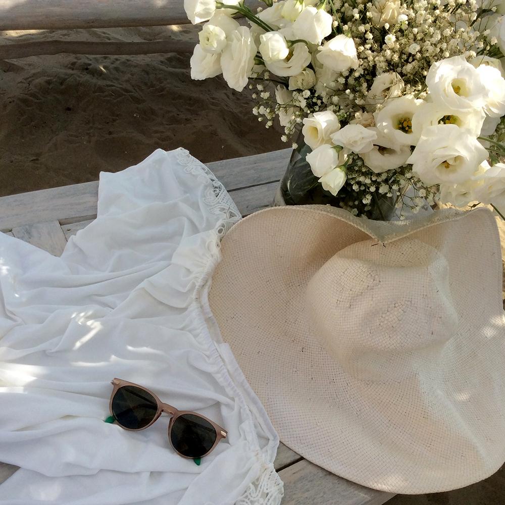 composizione fiori estate spiaggia con abito bianco, occhiali da sole, cappello e fiori bianchi